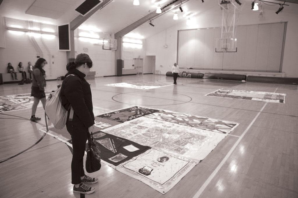 SOLEMN VISITATION:  Students observe pieces of the AIDS quilt on World AIDS Day on December 1. Portions of the 54-ton quilt were displayed in Ruby Scott Gym during tutorial.    Photo by: Joel Abrahams