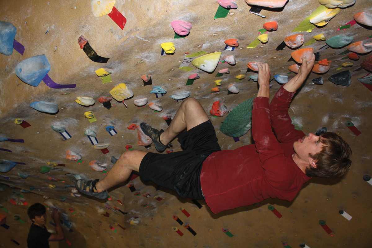 """THE BETA: Senior Dillon Charlton hangs from the ceiling in """"the cave"""" at Planet Granite in San Francisco. Photo by: William Choulos"""