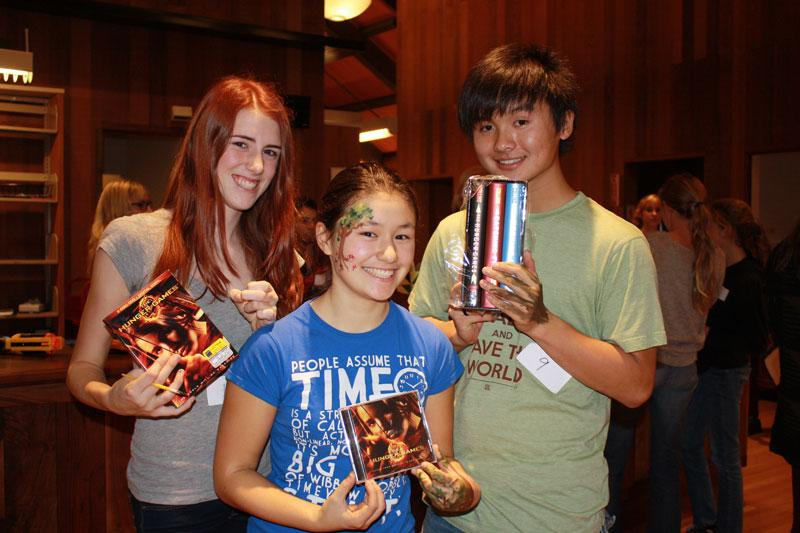 Junirs Cate Wilmoth, Grace Lightner, and Josh Leung display their prizes following the Hunger Games event.
