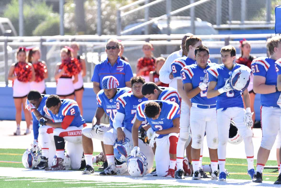 Varsity football players (left to right) seniors Tre'Chaun Berkley and Leonjae Silas, juniors Tristan Mitchell, Pedro Mira, and Oscar Corona, and senior Jordan Smith take a knee during the national anthem before the homecoming game against Redwood on October 8.                      PHOTO COURTESY OF HONG SOON PARK