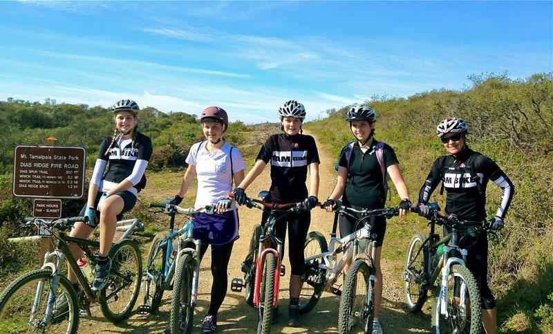RIDE HARD: Riders Lisa Martinez (sophomore), Amanda Moe (sophomore), Mae Puckett (sophomore), and Sophie McGuinness (senior) take a break with their coach, Christy Allen, while biking along Dias Ridge. Photo by: Blair Peterson