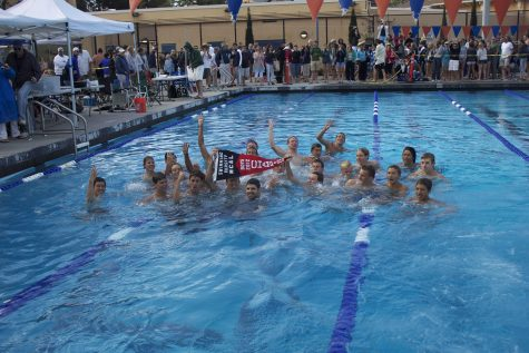 Boys swimming coach Dave Beutel joins the swimmers in the pool to celebrate their win. Photo by Kristie Lee