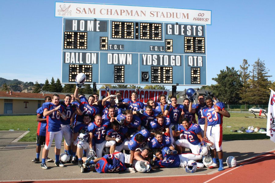 The+boys+varsity+football+team+poses+in+front+of+the+scoreboard+after+defeating+Drake+28-7+in+their+homecoming+game.