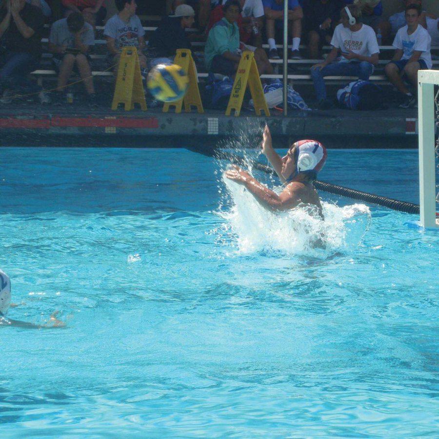 Junior Tristan Maass, starter on varsity water polo, reaches up to block a shot.