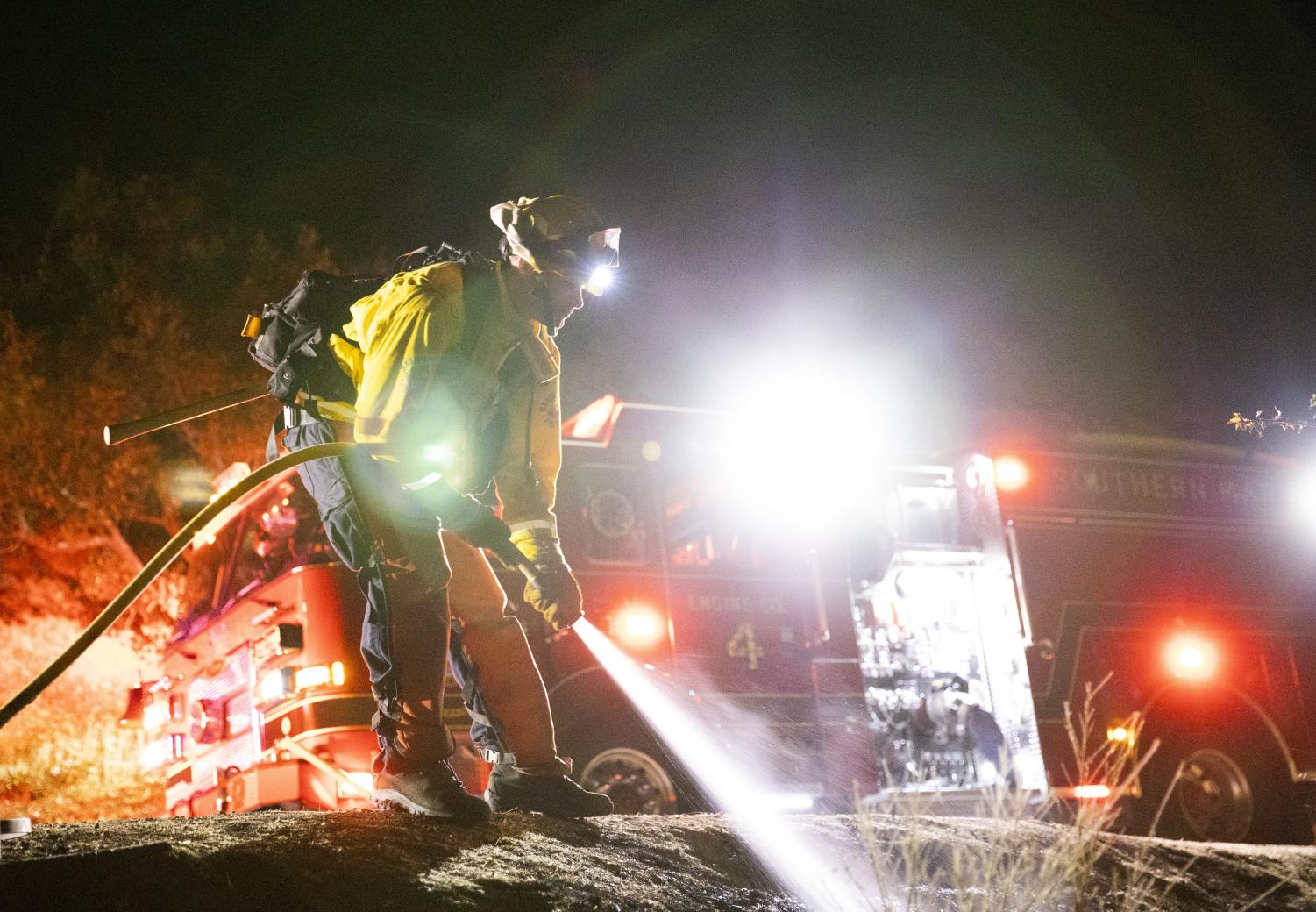 Marin County firefighters put out a small fire on Fern Canyon in Mill Valley the night before the power shutoff. (Ethan Swope)