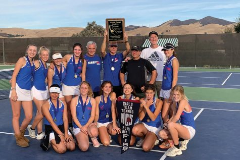 The girls varsity tennis team poses with their NCS banner after winning the NCS team tennis championship. (Courtesy of Tam Tennis)