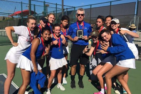 Former girls' and boys' tennis coach Bill Washauer poses with the girls' tennis team after a tournament victory last season. (Courtesy of Tenaya Tremp)