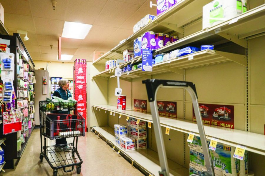 Shoppers collect toilet paper and paper towels to prepare for the COVID-19 outbreak, leaving store shelves empty. (Ethan Swope)